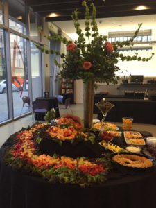 Fruits laid out beautifully on a table with a big flower centerpiece