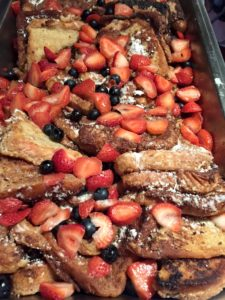 Deep fried French toast topped with strawberries and blueberries