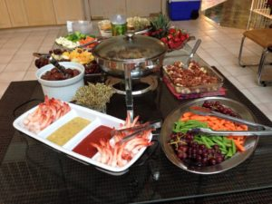 A table with various savory dishes and bowls of fruits