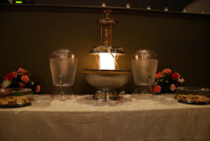 A lamp that looks like a fountain and two glass jugs of water